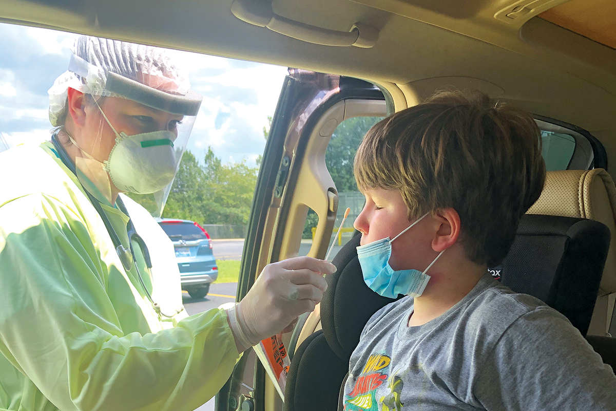 A boy in a car gets a COVID-19 test by a medical worker in full PPE