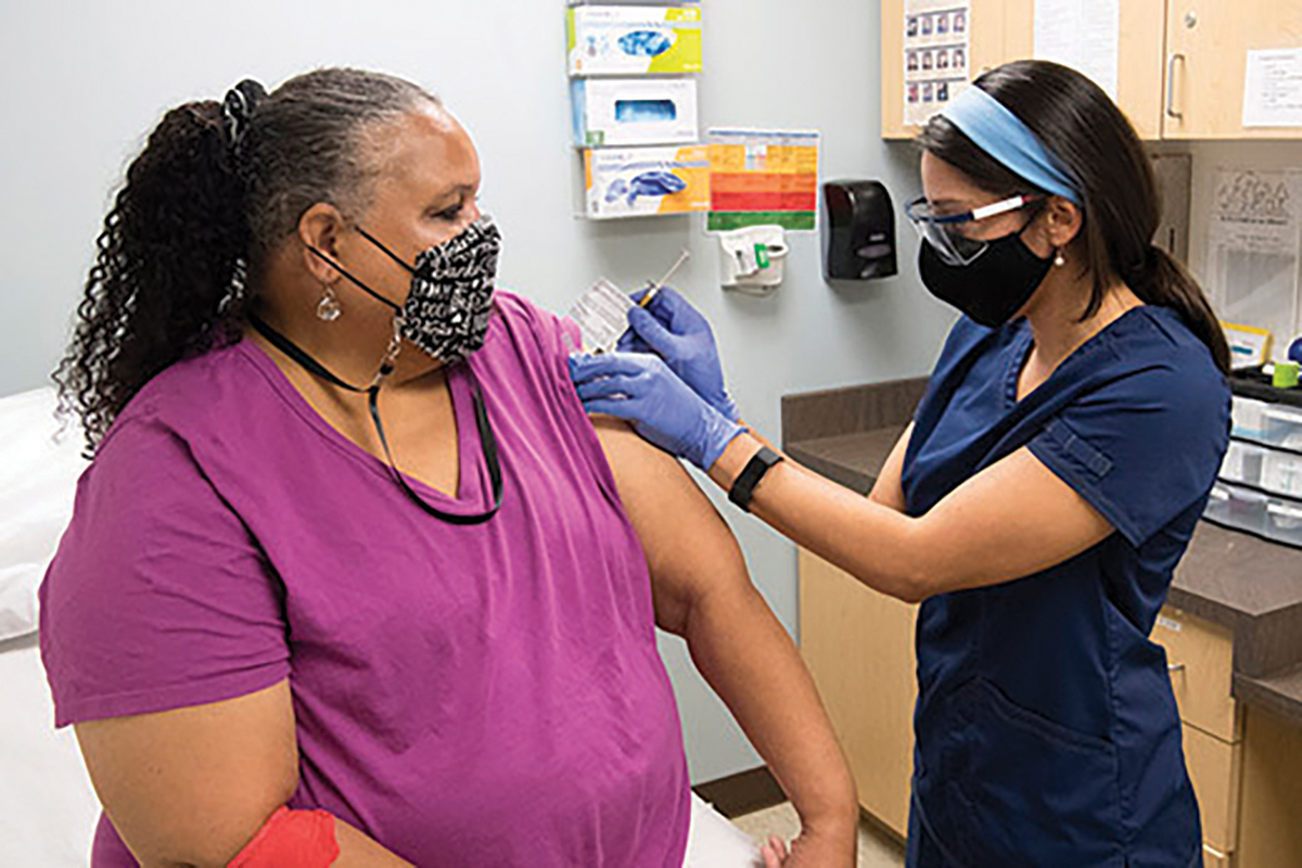 A nurse gives a COVID-19 vaccine dose to a volunteer.
