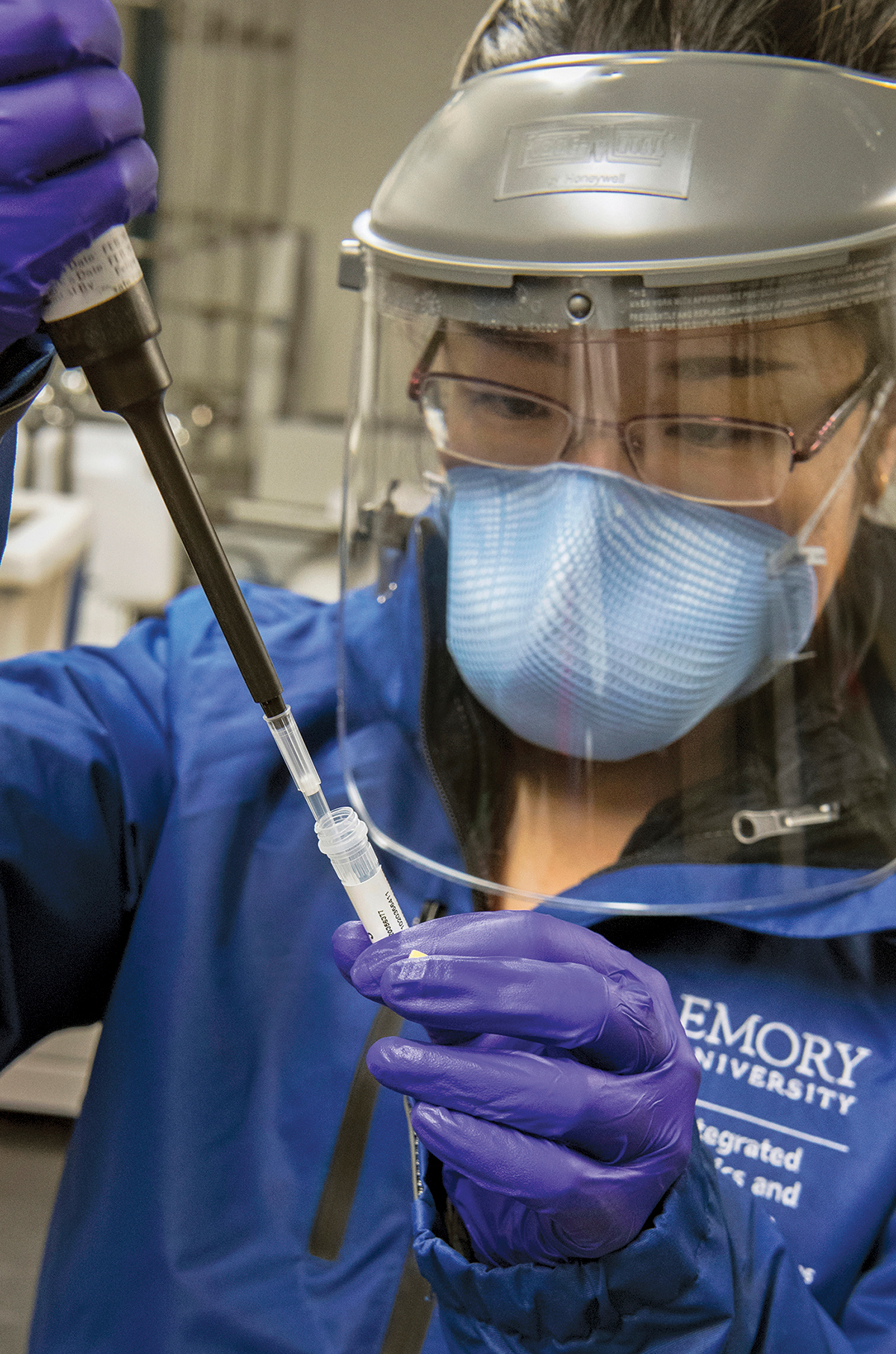a researchers in gloves and a face shield works with a small test tube and a long instrument.