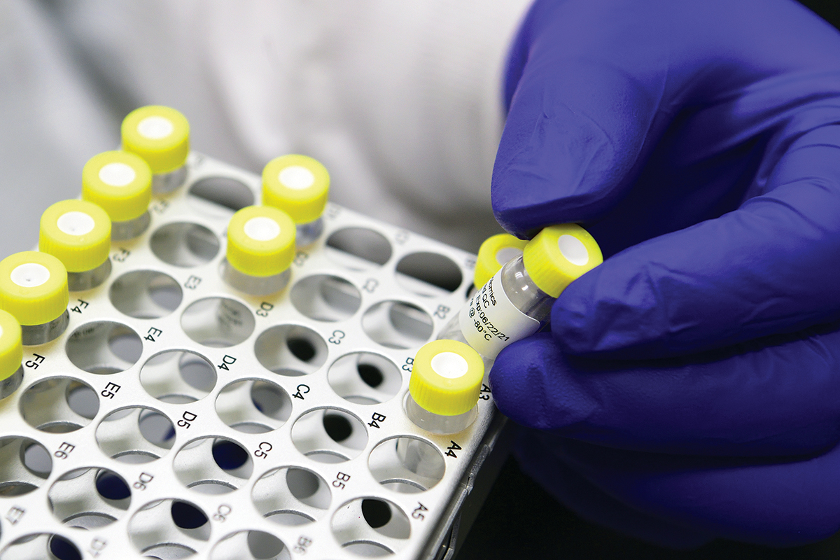 A purple, gloved hand holds a tiny yellow-capped bottle of an injectable from a tray of many identical bottles.