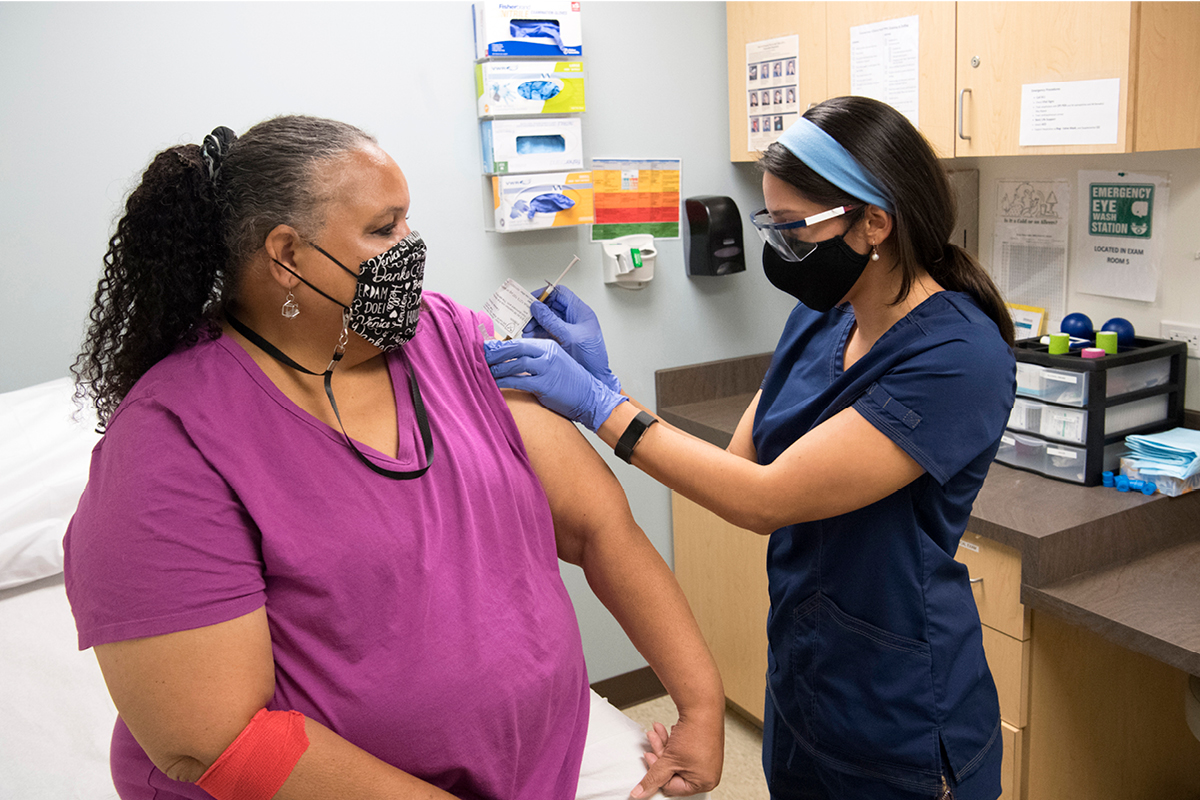 A woman wearing a purple shirt and a mask sits on an examination table and receives a shot from a female healthcare worker in blue scrubs, gloves, and headband.
