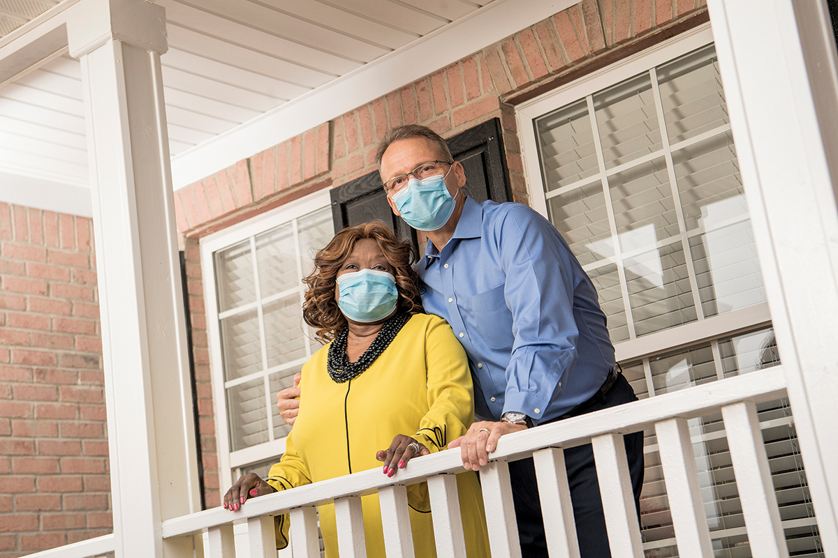 Claudette Himes and husband Leonard Himes stand together on a balcony, weaving COVID-19 masks.