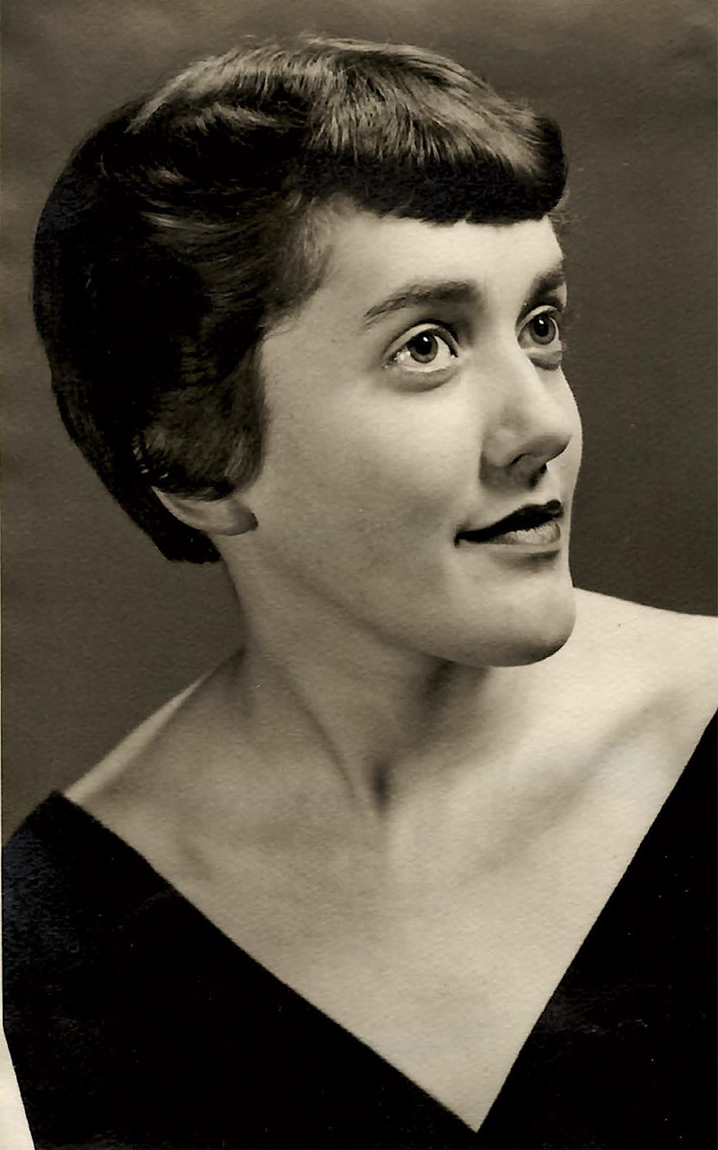 Pat Carini as a young woman in a sepia-toned portrait. She is wearing a black top with a v-shaped neckline.