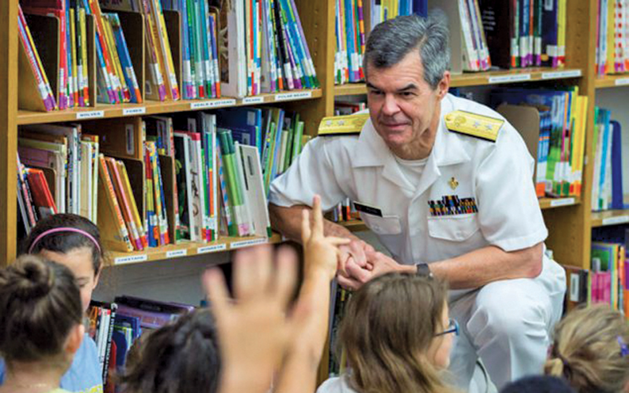 Stephen Redd in a white military style uniform kneels next to bookshelves. A group of children is in the foreground with their arms raised.
