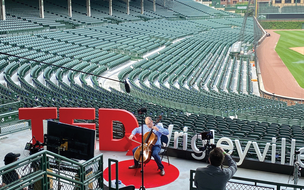 A man plays cello above empty seats at Wrigley Field. TEDxWrigleyville is spelled out in large cutout letters behind him.