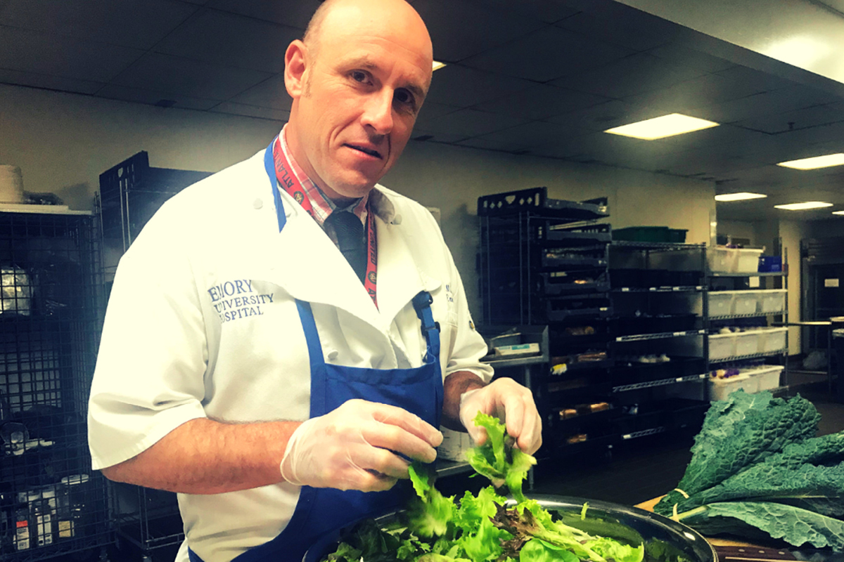 Photo of Mike Bacha, in the kitchen at Emory, wearing an apron and chef's jacket, preparing a salad.