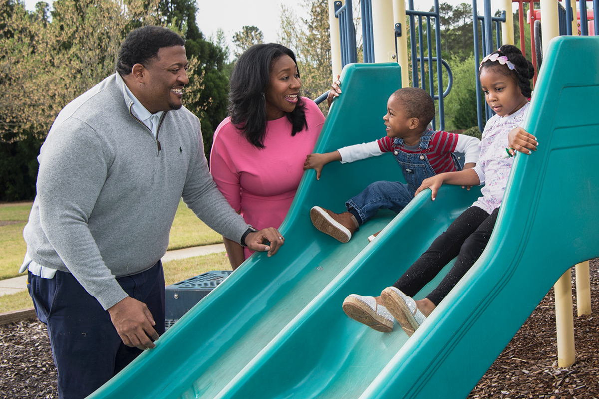 Photo of Jacynta Brewton and husband, smiling, helping their twin sons slide down a playground slide.