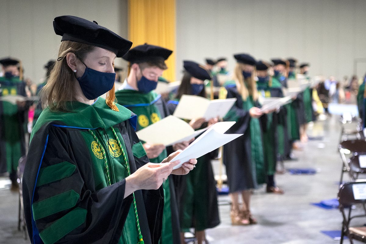 Photograph of nurses in green graduation regalia (academic robes) during a graduation ceremony.